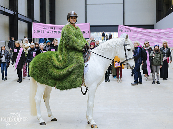 Culture Declares Emergency with banners, a white horse and a rider in a grass coat.